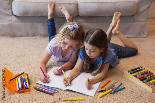 Siblings drawing in the living room