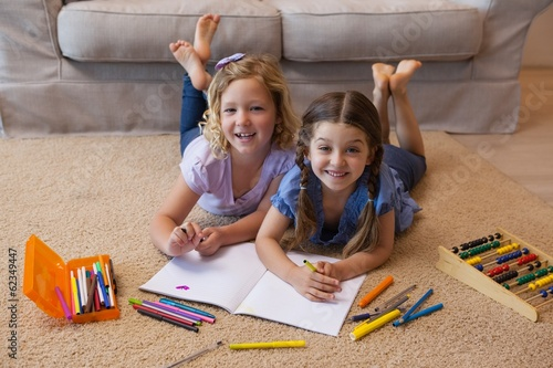 Full length portrait of siblings drawing in living room