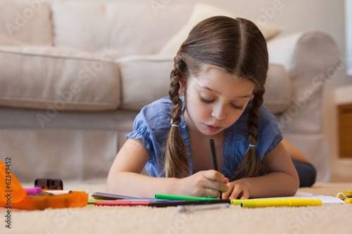 Close-up of a little girl drawing in living room