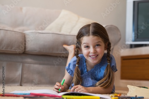 Portrait of a little girl drawing in living room