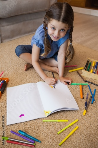 Full length of a little girl drawing in living room