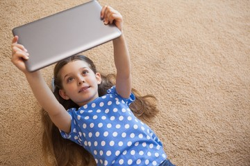 Little girl using digital tablet in the living room