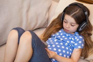 Girl listening music while using digital tablet in the living ro