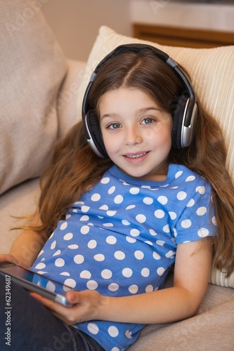 Little girl listening music while using digital tablet in living