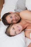 Happy relaxed young couple together in bed