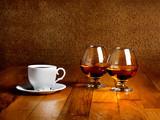 Two goblets of brandy and cup of hot coffee