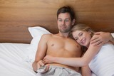 Loving relaxed young couple watching tv in bed