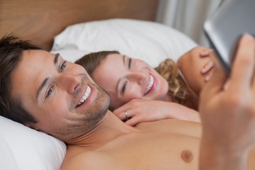 Relaxed young couple text messaging in bed