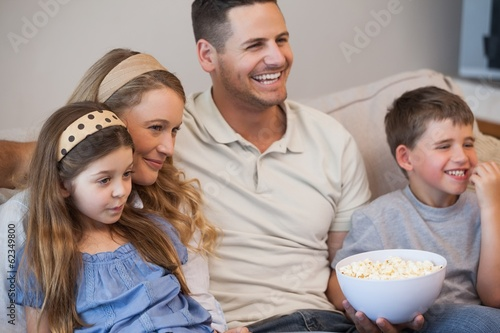 Cheerful family watching tv on sofa in living room