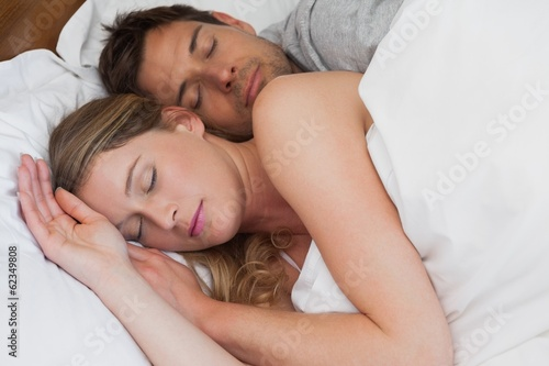 Relaxed couple sleeping together in bed