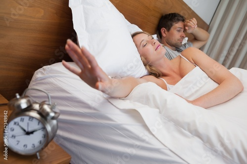 Couple in bed with alarm clock in foreground