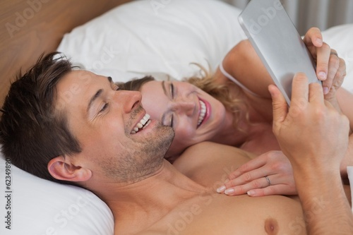 Happy relaxed couple with digital tablet in bed