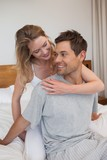 Loving relaxed young couple in bedroom