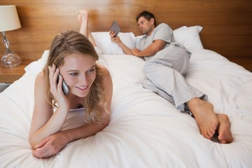 Woman using mobile phone and man with digital tablet in bed