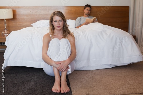 Sad woman with man reading book in background