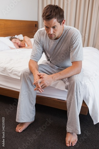 Sad man with woman sleeping in background