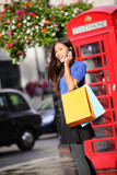 London woman talking on smartphone shopping