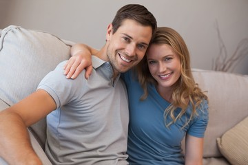 Portrait of a loving couple sitting on sofa
