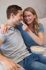 Young woman feeding man popcorn on sofa