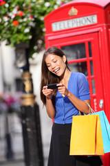 London woman on smart phone shopping