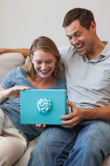Happy woman receiving a gift by man in living room