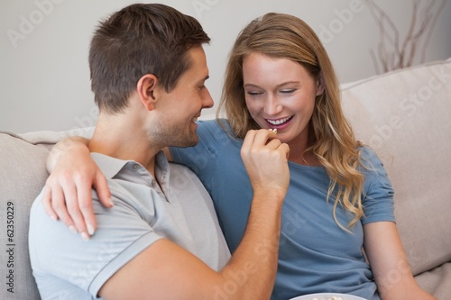 Loving man feeding woman popcorn on sofa