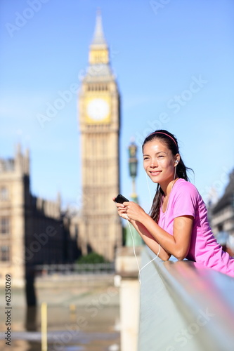 London woman runner listening to music by Big Ben