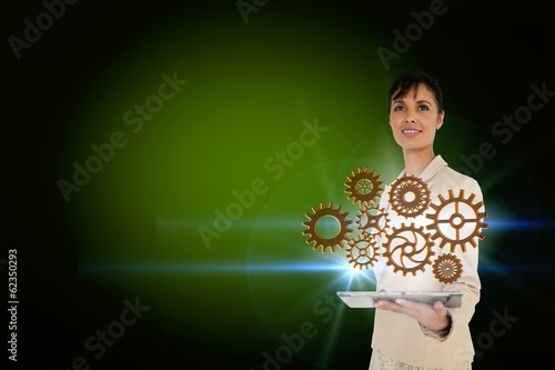 Businesswoman holding tablet with cogs and wheels