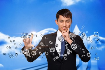 Thinking businessman touching cogs and wheels