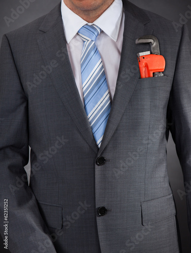 Businessman In Suit With Adjustable Wrench In Pocket