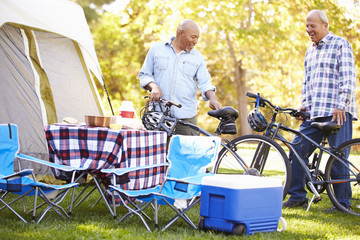 Two Senior Men Riding Bikes On Camping Holiday