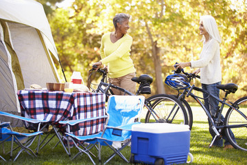 Two Mature Women Riding Bikes On Camping Holiday