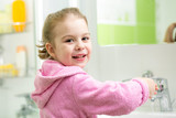 kid girl washing her hands in bathroom