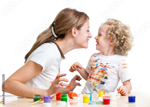 smiling mother and child girl painting together