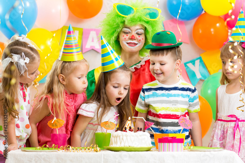 kids blowing candle on festive cake