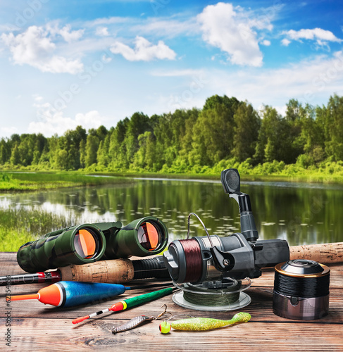 fishing tackle on a pontoon on the background of the lake - 62354656