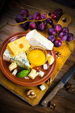 .Different varieties of cheese with walnuts and grapes