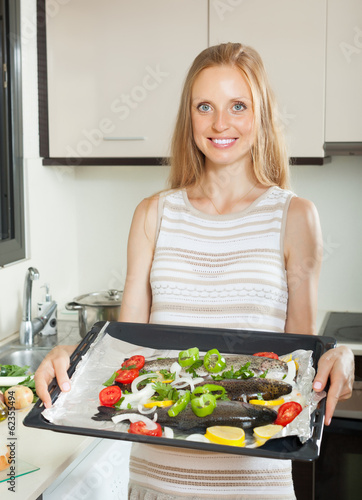 Smiling housewife cooking fish