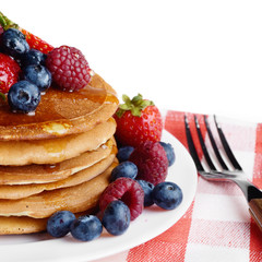 Pancakes with berries and honey over white