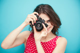 beautiful girl with vintage photo camera on a blue background in