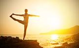 Fototapety woman doing yoga on the beach at sunset