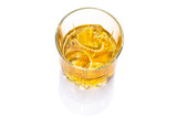 Glass of scotch whiskey on ice over white background