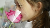 smiling little girl smelling a red rose, close-up