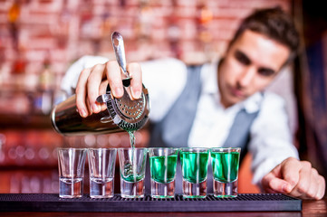 Bartender pouring blue curacao alcoholic cocktail in glasses