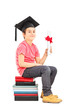 Boy sitting on stack of books and holding diploma