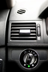 Car ventilation system and headlight adjustment on dashboard