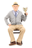 Elderly gentleman sitting on a chair and holding a trophy