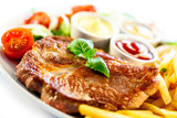 Grilled steaks, French fries and vegetables (shallow DOF)