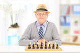 Elderly gentleman posing behind a chessboard at home