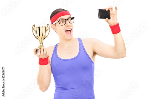 Male athlete taking picture of himself holding a trophy